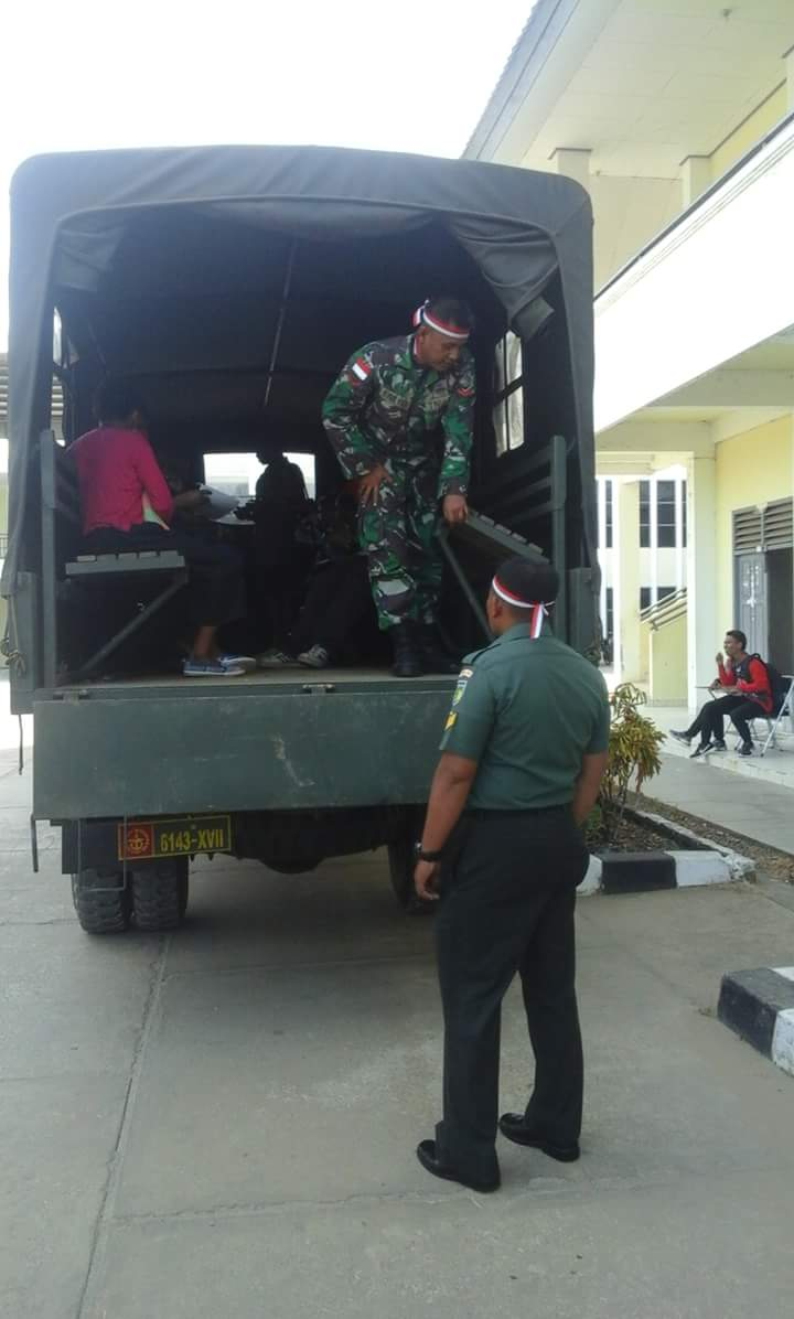Komandan Pasukan TNI sedang memastikan Mahasiswa Papua penerima Beasiswa Bidik Misi harus naik ke Truk TNI. Sementara Mahasiswa Non Papua yang sedang duduk di samping dinding gedung dibiarkan.@Manuel Metemko.